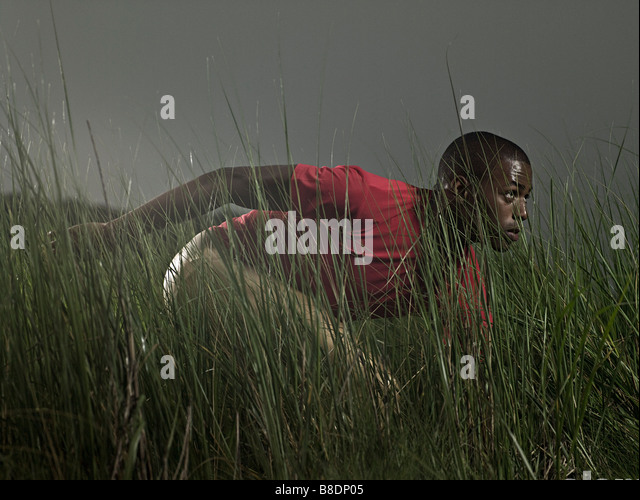 Male athlete in grass - Stock Image