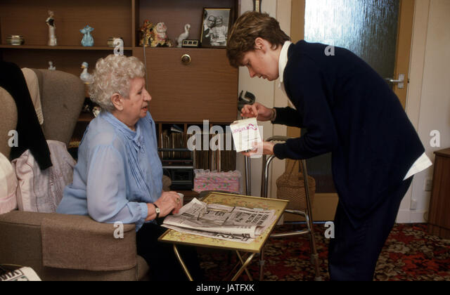 Health visitor assisting an elderly woman with her medication - Stock Image