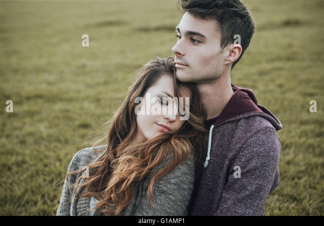 Young teenagers outdoors, sitting on the grass and cuddling, he is hugging his girlfriend, relationships and feelings - Stock-Bilder