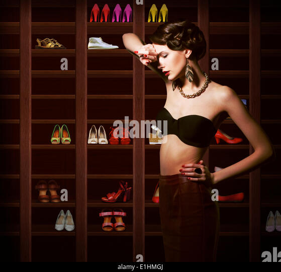 Confusion. Upset Woman Choosing what to Wear. Wardrobe with Footwear - Stock Image