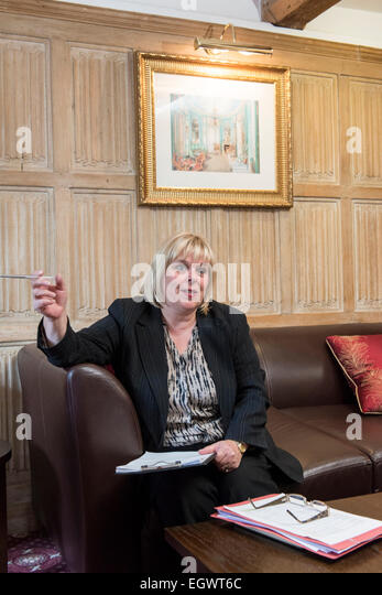 a professional business woman / wedding planner conducts a coffee table meeting with a client in an english country - Stock Image