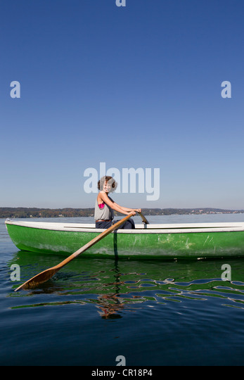 Woman rowing boat in still lake - Stock Image