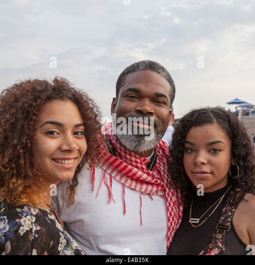 A father stands with his two daughters at Summerfest, an annual music festival held in Milwaukee, Wisconsin USA. - Stock-Bilder