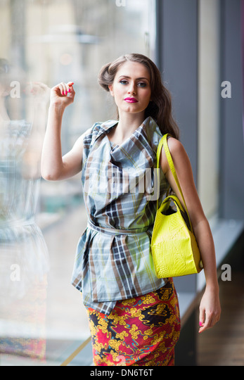 A teenage brunette girl wearing a tartan style top and floral wrap-around skirt with a yellow handbag. - Stock-Bilder