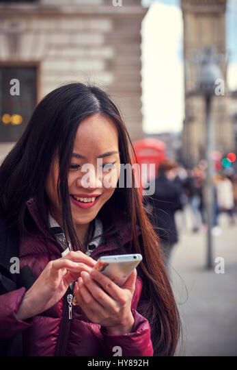 A young Japanese woman using her smart phone in London - Stock Image