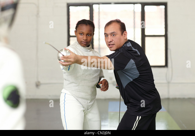 Fencing tutor assisting female student - Stock Image