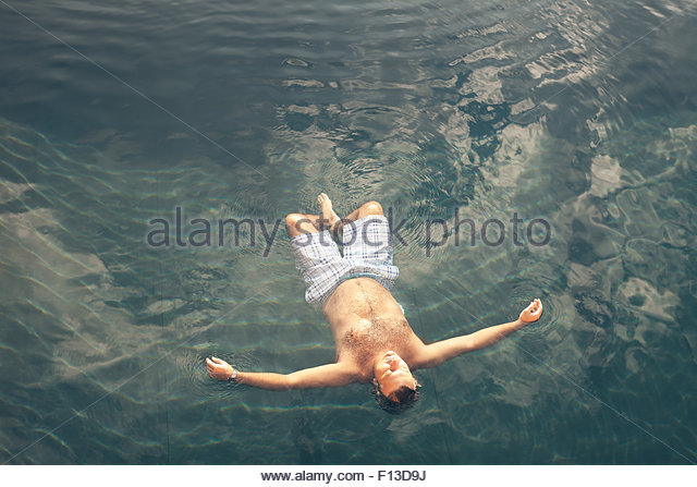 Man floating in a swimming pool - Stock Image