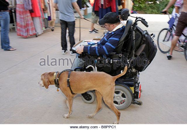 Miami Beach Florida Lincoln Road Mall pedestrian Antiques and Collectibles Market man electric wheelchair equipment - Stock Image