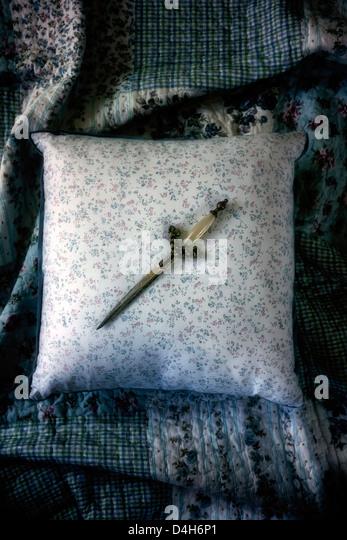 a dagger on a vintage pillow - Stock-Bilder