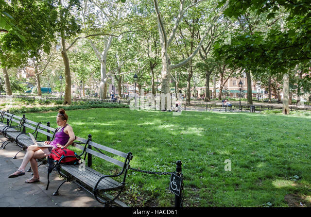 Manhattan New York City NYC NY Greenwich Village Washington Square Park public park bench woman laptop sitting lawn - Stock Image