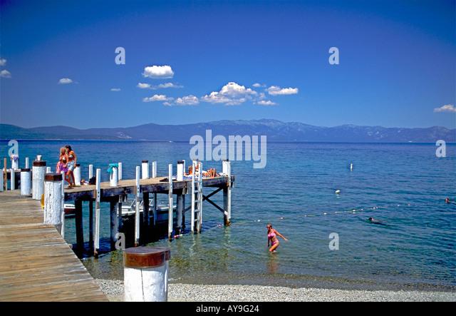 Swimming boating and sunbathing Lake Tahoe California.  Girls, women  20's in bikini's, dock, boat pier, - Stock Image