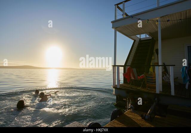 Young adult friends swimming near summer houseboat on sunset ocean - Stock-Bilder