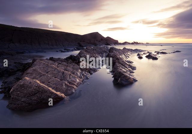 Long exposure of waves moving over rocks on Crackington Haven Beach at sunset, Cornwall, England, United Kingdom, - Stock Image