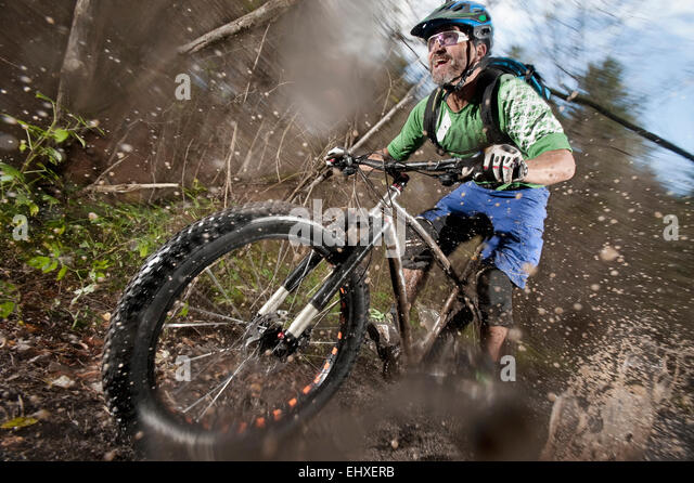 Mountain biker riding on a dirt road, Bavaria, Germany - Stock-Bilder