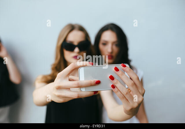Two girlfriends taking a selfie - Stock Image