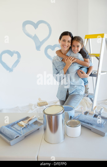 Mother and daughter hugging among paint supplies - Stock Image