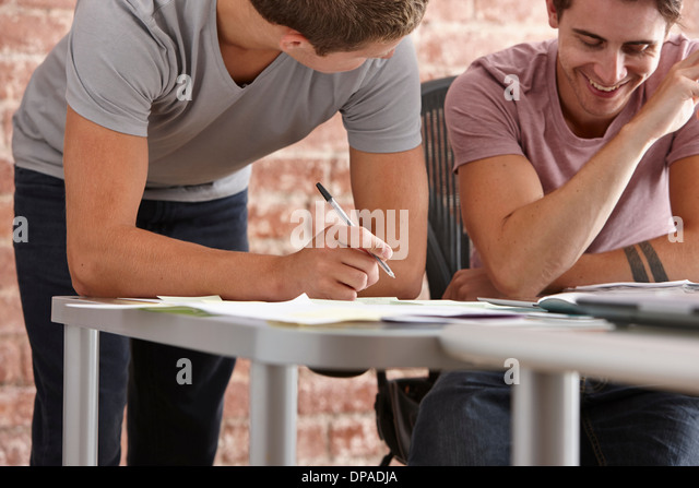 Two male colleagues, one making notes - Stock Image