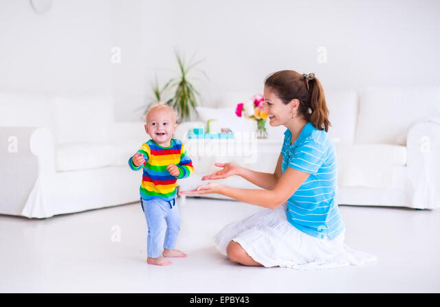 Cute little baby boy making his first steps, walking to his mother in a white sunny living room - Stock Image