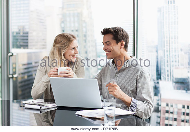 Business people using laptop together - Stock Image