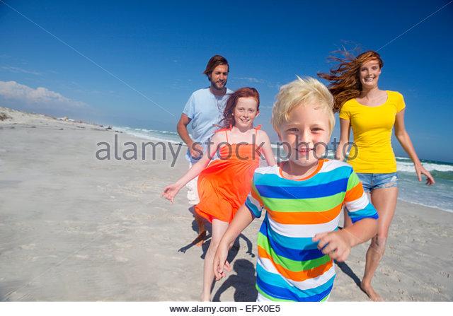 Happy family running toward camera, on sunny beach - Stock Image