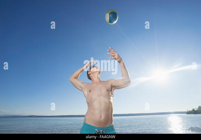 Mature man playing volleyball on the lake, Bavaria, Germany - Stock Image