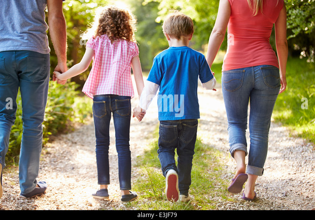 Rear View Of Family Walking In Countryside - Stock Image