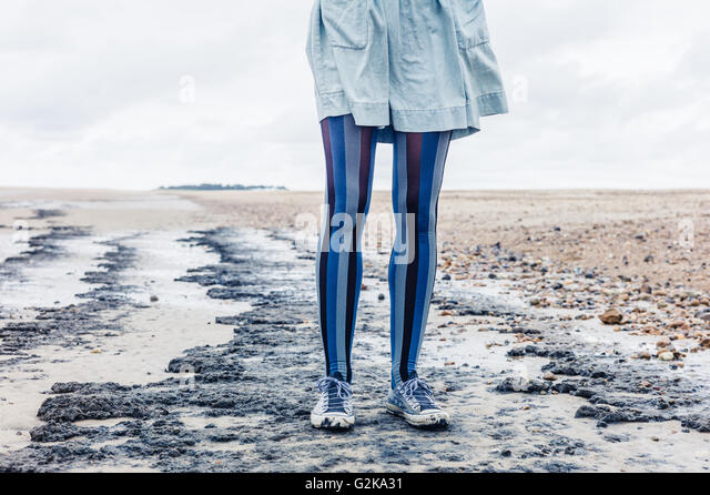 The legs of a young woman as she is standing on the beach with her skirt blowing in the wind - Stock Image