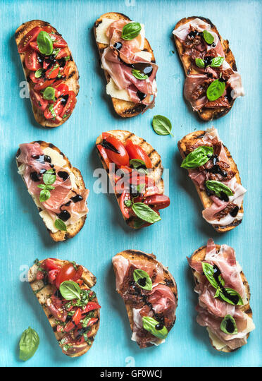 Brushetta set for wine. Variety of small sandwiches on turquoise blue backdrop, top view - Stock Image