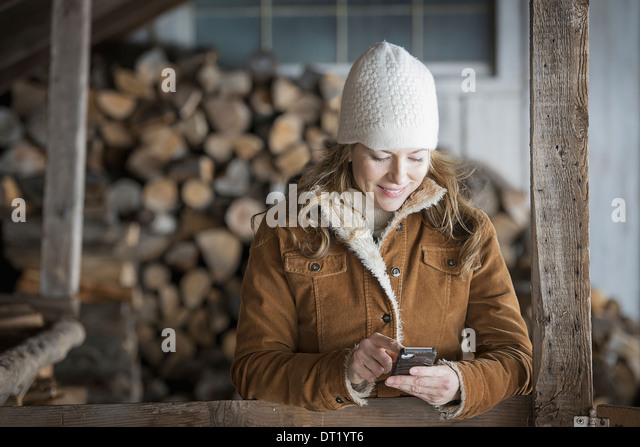 An organic farm in upstate New York in winter A woman in sheepskin coat and woollen hat using a cell phone - Stock Image
