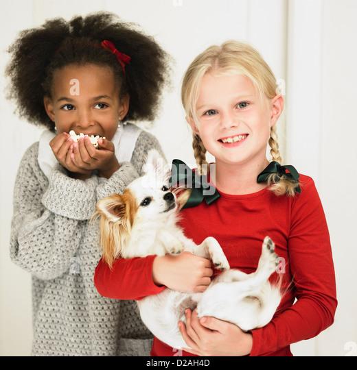 Girls eating popcorn and holding dog - Stock Image
