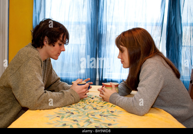 Teen couple talking over coffee or tea, at a yellow table. - Stock Image