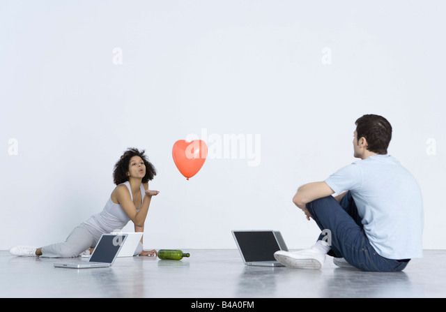 Man and woman playing spin the bottle with laptop computers - Stock-Bilder