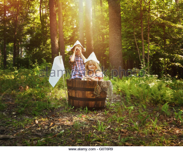 A little boy and girl are pretending to fish in a wooden barrel boat in the nature woods with a fish for an imagination - Stock Image