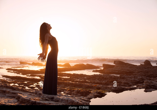 Beautiful woman by the sea at sunset. - Stock Image
