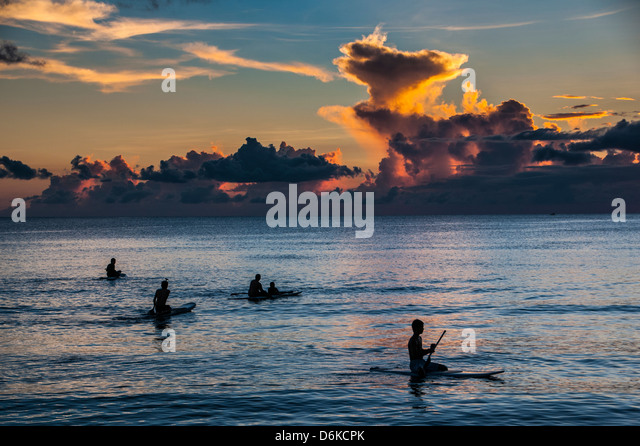Surfer at sunset in Guam, US Territory, Central Pacific, Pacific - Stock Image