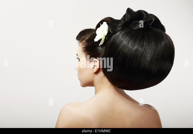 Haircare. Backside of Fashion Model with Creative Hairstyle. Smooth Healthy Black Hair with Flower. Spa Salon - Stock Image