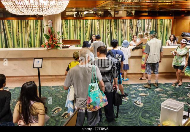 Waikiki Beach Honolulu Hawaii Hawaiian Oahu Pacific Beach Hotel hotel lobby line queue guests front desk checking - Stock Image