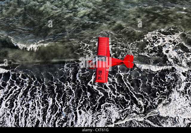 Aerial view, a red single-engine lightweight airplane flying over the waves of the North Atlantic, black lava coast, - Stock Image