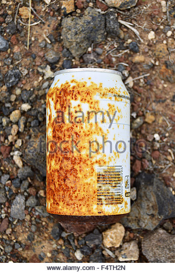Trashed corroded aluminum can on the ground - Stock Image