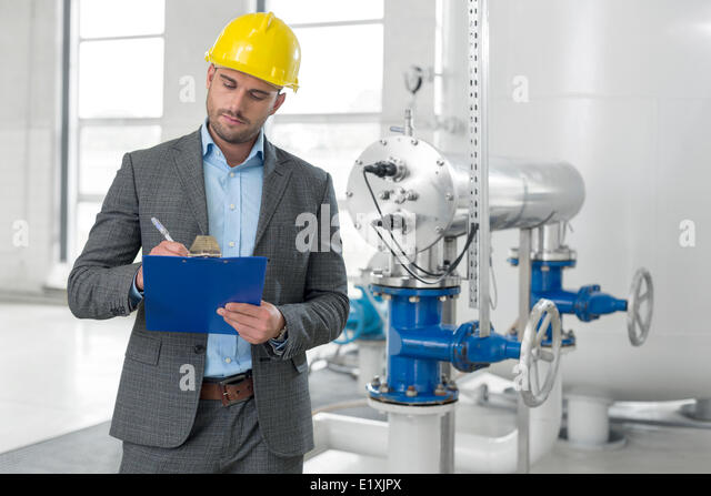 Young male manager writing on clipboard in industry - Stock Image