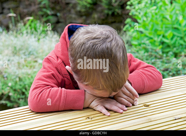 Boy, two years old, sitting at a table and feeling sad - Stock Image