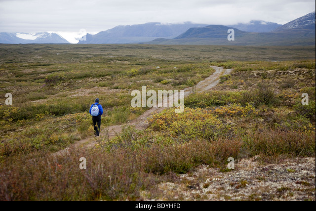 A woman hikes across the alpine tundra on the Maclaren Summit Trail in Alaska - Stock Image