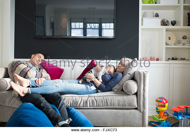 Parents and baby son sleeping on sofa - Stock Image