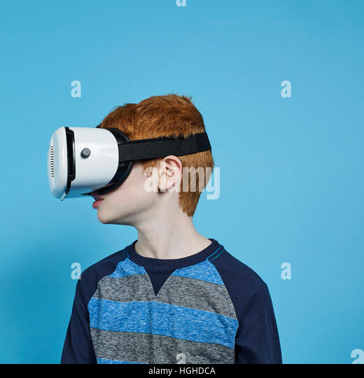profile of young boy wearing VR headset, VR Glasses - Stock Image