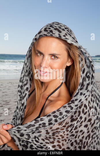 Portrait of smiling woman on beach wrapped in leopard print scarf, Cape Town, South Africa - Stock Image