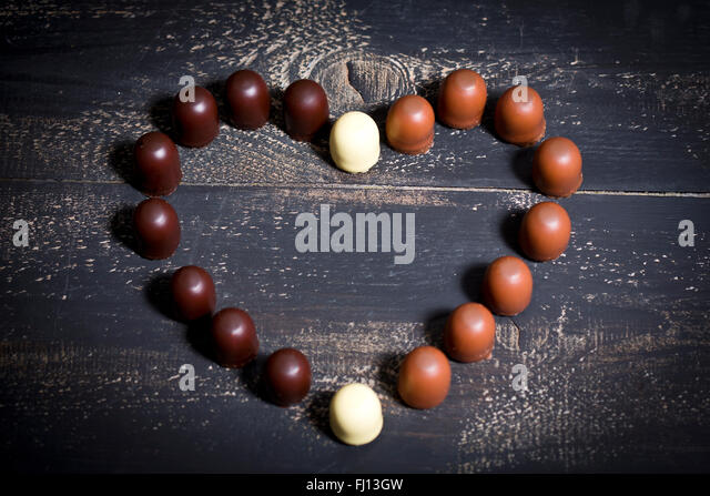 Different chocolate marshmallows forming a heart on dark wood - Stock Image