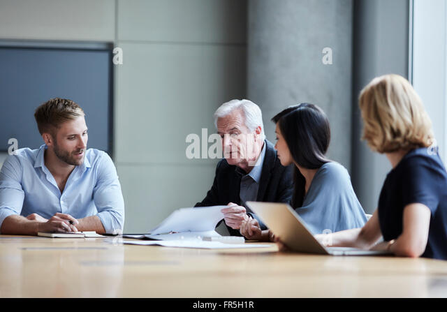 Business people discussing paperwork in conference room - Stock-Bilder