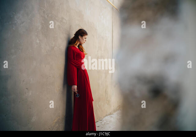 Caucasian woman wearing red dress leaning on wall in alley - Stock Image