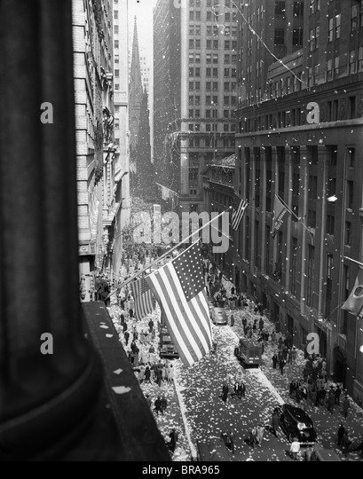 1940s 1945 AERIAL VIEW OF VE DAY CELEBRATION ON WALL STREET NYC WITH FLAGS AND CONFETTI FLYING - Stock Image