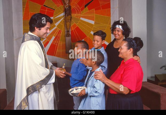 Three 3 Generation interracial inter racial Hispanic family of 5 presents gifts of the Eucharist to Hispanic priest - Stock-Bilder